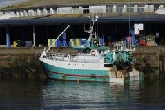Modernes Fischerboot koppelte im Hafen von Lorient, Frankreich mit Lager im Hintergrund an Lizenzfreies Stockfoto