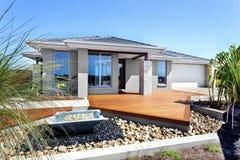 Modernes Haus mit Bäumen und Steindekorationseinzelteilen lizenzfreie stockbilder