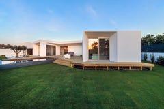 Modernes Haus mit GartenSwimmingpool und hölzerner Plattform lizenzfreie stockfotos