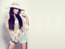 Modernes junges Brunettemädchen, das im weißen Hut aufwirft. Lizenzfreies Stockbild