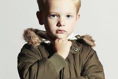 Modernes Kind im Wintermantel Kinder in der erwachsenen Kleidung Kinder kakifarbiger Parka Little Boy Stockfotografie