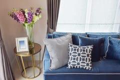 Modernes klassisches Sofa des Marineblaus und Retro-, graue und blaue Kissen mit einem reizenden Orchideenvase Stockbild