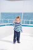 Modernes kleines Baby auf Yacht im Marinehemd, Hosen Stockfoto