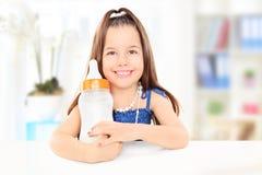 Modernes kleines Mädchen, das eine Babyflasche voll von der Milch hält Stockbild