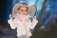 Modernes kleines Mädchen, das einen Hut und Sonnenbrille trägt Reisenkoffer mit Meerblick nach innen Stockfotos