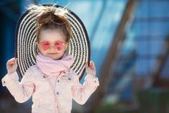 Modernes kleines Mädchen, das einen Hut und Sonnenbrille trägt Reisenkoffer mit Meerblick nach innen Stockbilder