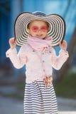 Modernes kleines Mädchen, das einen Hut und Sonnenbrille trägt Reisenkoffer mit Meerblick nach innen Stockfotografie