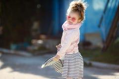 Modernes kleines Mädchen, das einen Hut und Sonnenbrille trägt Reisenkoffer mit Meerblick nach innen Lizenzfreie Stockbilder