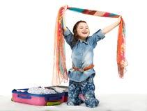 Modernes kleines Mädchen, das einen Koffer auspackt Lizenzfreie Stockbilder