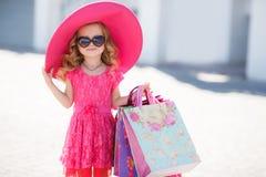 Modernes kleines Mädchen in einem Hut mit Einkaufstaschen Lizenzfreie Stockfotos