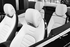 Modernes Luxusauto nach innen Innenraum des modernen Autos des Prestiges Bequeme Ledersitze Weißes perforiertes ledernes Cockpit  lizenzfreie stockbilder