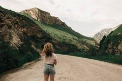 Modernes Mädchen in der weißen Kleidung, die auf der Straße in den Hochländern steht Grünes Gras und Berge lizenzfreie stockfotos