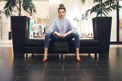 Modernes Mädchen auf der schwarzen Couch Stockbild