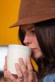 Modernes Mädchen, das von der Kaffeetasse trinkt Stockfotos