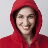 Modernes Mädchen der Strahlung 20s, das an einen Hoodie für Kühle trägt Lizenzfreies Stockfoto