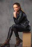 Modernes Mädchen im Leder, das im Studiohintergrund aufwirft stockfoto
