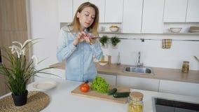 Modernes Mädchen macht Foto vom Gemüse am intelligenten Telefon für soziales Lizenzfreies Stockbild