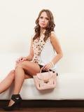 Modernes Mädchen mit der Handtasche, die auf Sofa sitzt Stockfotos