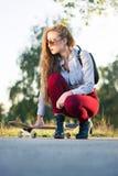 Modernes Mädchen mit einem Skateboard im Park lizenzfreies stockbild