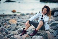 Modernes M?dchen gekleidet in der wei?en Jacke und breiten in der Hose, die nahe Meer am Abend aufwirft lizenzfreies stockfoto