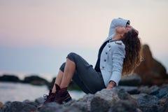 Modernes M?dchen gekleidet in der wei?en Jacke und breiten in der Hose, die nahe Meer am Abend aufwirft lizenzfreie stockfotos