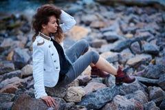 Modernes M?dchen gekleidet in der wei?en Jacke und breiten in der Hose, die nahe Meer am Abend aufwirft stockbild