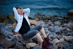 Modernes M?dchen gekleidet in der wei?en Jacke und breiten in der Hose, die nahe Meer am Abend aufwirft lizenzfreies stockbild