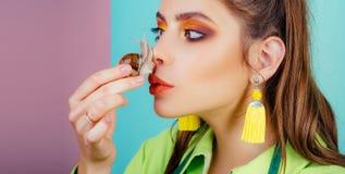 Modernes Make-upgesicht des M?dchens und nette Schnecke Cosmetologysch?nheitsverfahren Zutreffen des transparenten Lacks Massage  lizenzfreies stockfoto