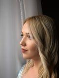 Modernes Mädchen der jungen stilvollen Frau, das durch Fenster schaut Lizenzfreies Stockfoto
