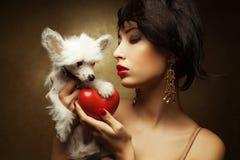 Modernes Modell, das rotes Herz und weißen kleinen chinesischen Hund mit Haube hält Stockfotos