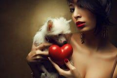 Modernes Modell, das rotes Herz und weißen kleinen chinesischen Hund mit Haube hält Stockfotografie