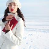 Modernes Modell im weißen Mantel nahe Wintermeer lizenzfreie stockfotos