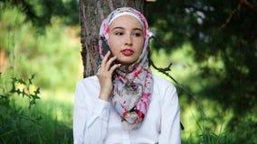 Modernes moslemisches Mädchen, das auf beweglichem im Freien spricht stock video footage
