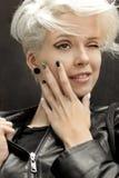 Modernes Nageldesign mit Schwarzweiss-Lack auf einem lächelnden blonden Mädchen stockfoto