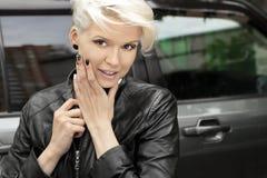 Modernes Nageldesign mit Schwarzweiss-Lack auf einem lächelnden blonden Mädchen stockbilder