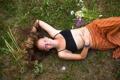 Modernes nettes Mädchen, das zurück auf seinem mit ihrem Haar unten auf dem Gras liegt Lizenzfreie Stockbilder
