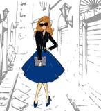 Modernes nettes Mädchen in einer Lederjacke, blauen in einem Midi-Rock und in Schuhen gehend hinunter die Straße Stockbilder