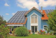 Modernes neues gebautes Haus und Garten, Dachspitze mit den Solarzellen, blau Lizenzfreie Stockbilder