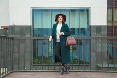 Modernes Porträt der jungen Frau im Smaragdkleid, Weiß strickte Strickjacke und Marsals-Hut Stockfotografie