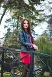 Modernes Porträt des Herbstes des roten Lippenstifts des jungen glücklichen Brunettemädchens draußen in der Stadt Lizenzfreies Stockfoto