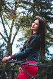 Modernes Porträt des Herbstes des roten Lippenstifts des jungen glücklichen Brunettemädchens draußen in der Stadt Lizenzfreie Stockfotos