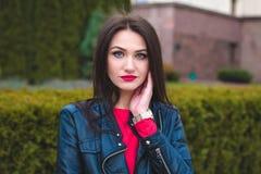 Modernes Porträt des Herbstes des roten Lippenstifts des jungen glücklichen Brunettemädchens draußen in der Stadt Stockbilder