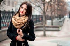 Modernes Porträt des Herbstes des roten Lippenstifts des jungen glücklichen Brunettemädchens draußen in der Stadt Stockfoto