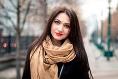 Modernes Porträt des Herbstes des roten Lippenstifts des jungen glücklichen Brunettemädchens draußen in der Stadt Lizenzfreies Stockbild