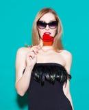 Modernes schönes Mädchen, das einen roten Lutscher und einen Blick an seinem beißt In einem schwarzen Kleid auf einem grünen Hint Stockfotos