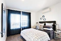 Modernes Schlafzimmer belichtet mit Sonnenlicht durch den Vorhang Stockfoto