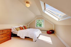Modernes Schlafzimmer des Dachbodens mit weißem Bett und Oberlicht. Stockfotografie