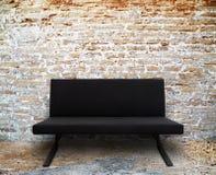 Modernes Sofa im alten Backsteinmauerraum Stockfotografie