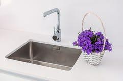 Modernes Spülbecken und Hahn mit dekorativen Blumen stockfotografie