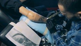 Modernes tattooer arbeitet mit dem behinderten Kunden und zeichnet auf prothetische Hand stock video footage